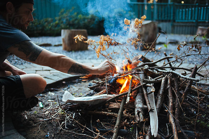 A caucasian man building a campfire outdoors in the evening. by J Danielle Wehunt for Stocksy United