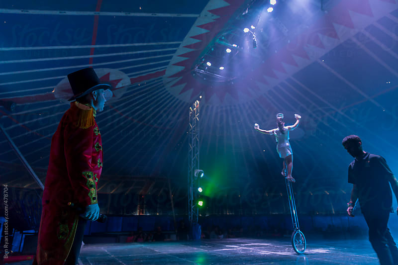 Circus performer on unicycle on stage with ring master and stage hand by Ben Ryan for Stocksy United