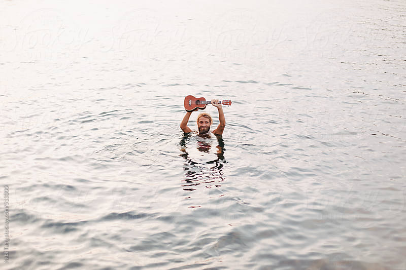Man in the ocean with ukulele by Nabi Tang for Stocksy United