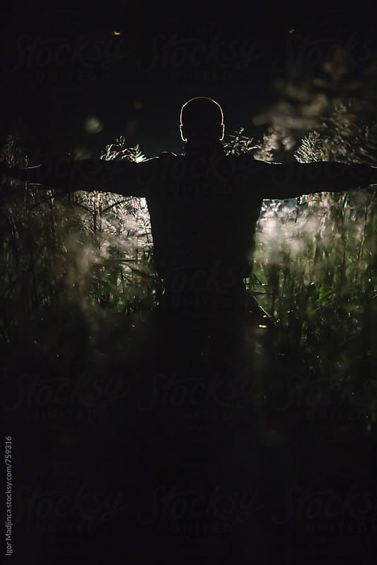 dark silhouette of a man in a field by Igor Madjinca for Stocksy United