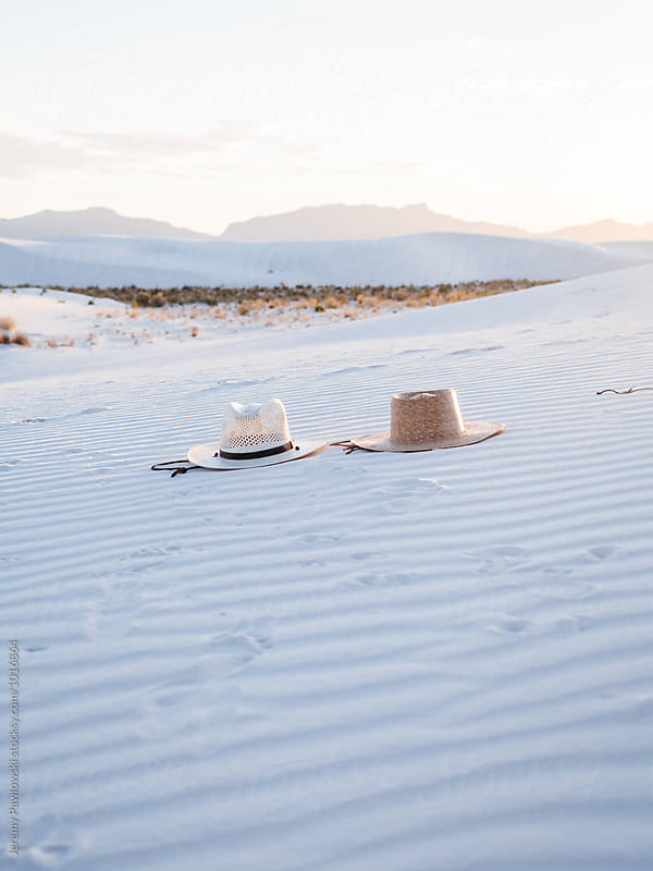 Couples straw hats laying in white sand with mountains in distance by Jeremy Pawlowski for Stocksy United