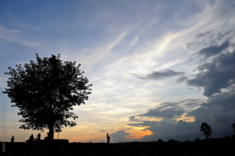 Silhouette of a tree and woman walking with dramatic cloud formation at sunset by Saptak Ganguly for Stocksy United