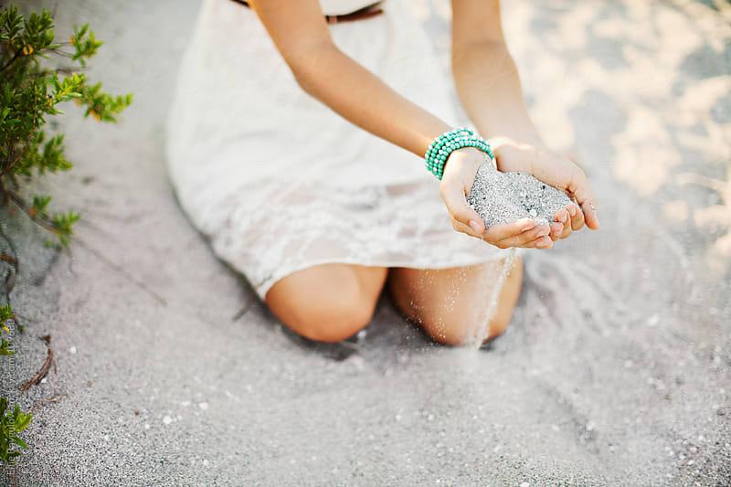 Girl holding sand by Ellie Baygulov for Stocksy United