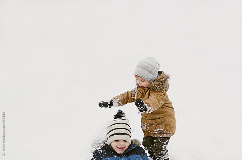 Two Boys Throwing Snow. by Ali Deck for Stocksy United
