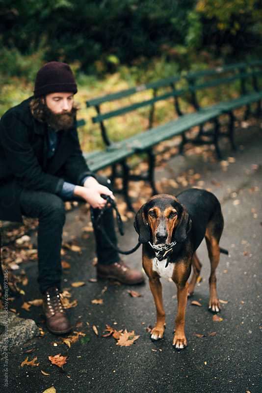 Man sitting with dog by Isaiah & Taylor Photography for Stocksy United