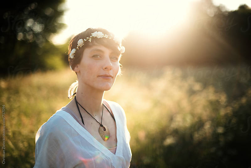 a girl wearing a flower crown in sunset light by Chris Zielecki for Stocksy United