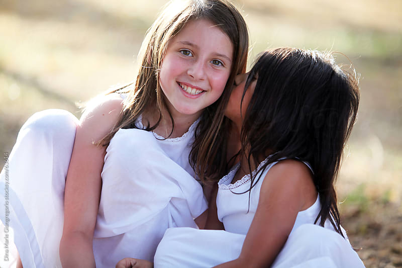 Two young girls in white dresses, one smiling while the other kisses her cheek by Dina Giangregorio for Stocksy United