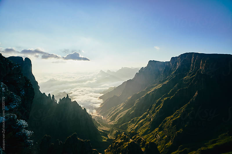 A summit view of a beautiful wild and mountainous landscape at sunrise. by Jacques van Zyl for Stocksy United