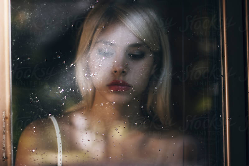 Beautiful girl standing at the window watching the rain by Jovana Rikalo for Stocksy United