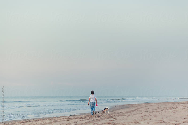 Boy walking on the beach with a beagle dog on a leash by Cindy Prins for Stocksy United
