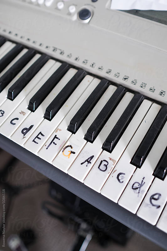 Keyboard with musical notes written on it by Rowena Naylor for Stocksy United