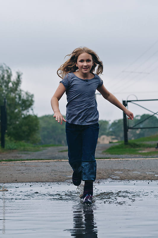 young girl running through puddles by Gillian Vann for Stocksy United