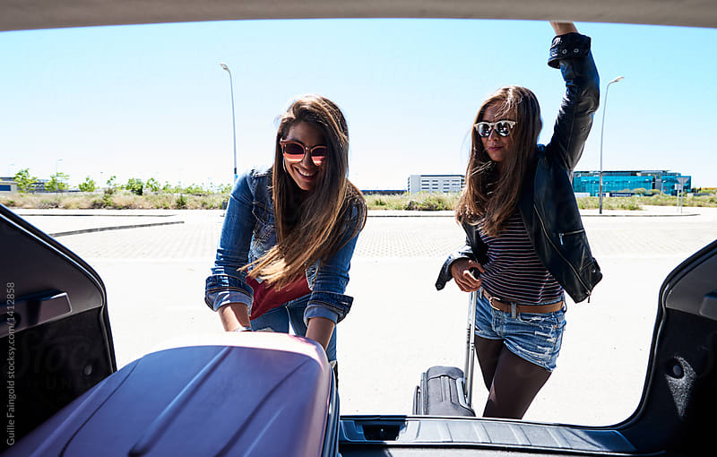 Happy girls unloading car of baggage. by Guille Faingold for Stocksy United