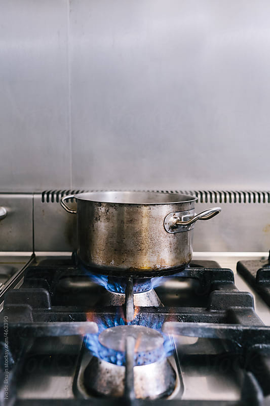 A pan with water being heated on a stove  by Ivo de Bruijn for Stocksy United