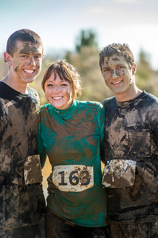 Teammates Cheerful Portrait After Mud Endurance Challenge by Brian McEntire for Stocksy United