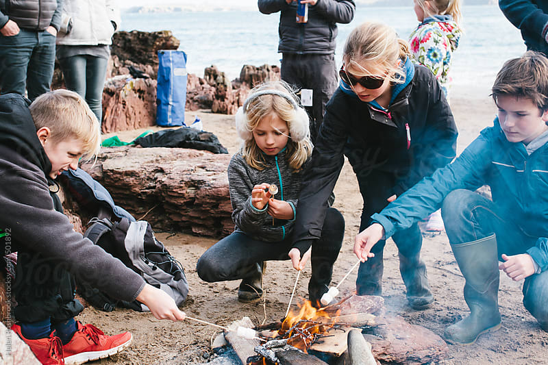 A group of friends toasting marshmallows over a fire on a beach. by Helen Rushbrook for Stocksy United