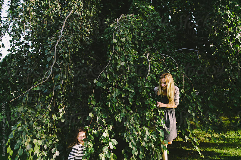 Mother and daughter playing and hiding among the branches by Evgenij Yulkin for Stocksy United