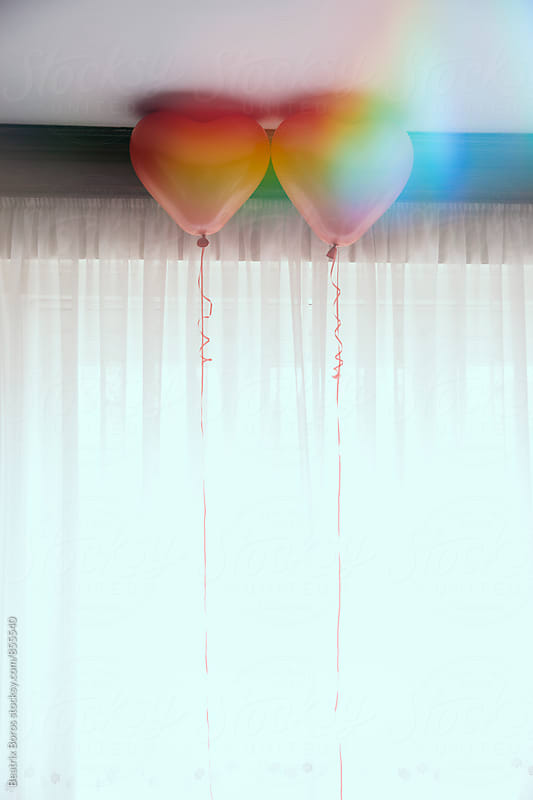 Double exposure of two balloons by a window by Beatrix Boros for Stocksy United