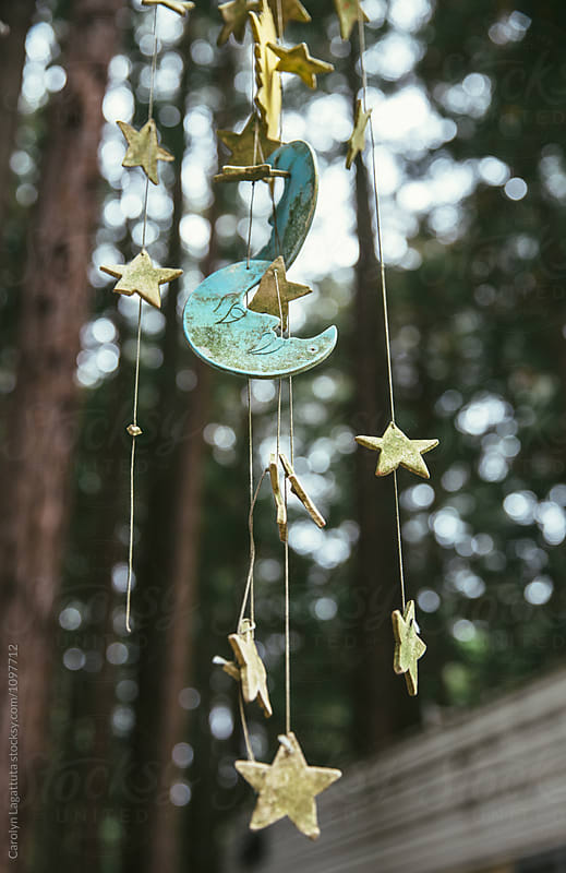 Star and moon mobile wind chime outside by Carolyn Lagattuta for Stocksy United