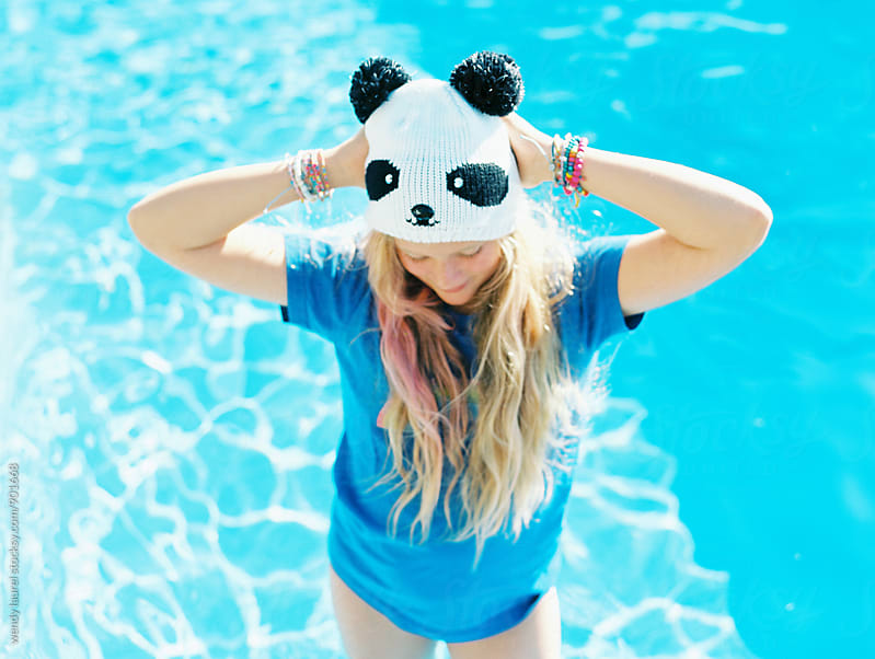 panda hat with hands on head with blonde girl in swimming pool in summer by wendy laurel for Stocksy United