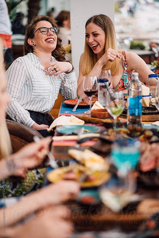 Friends having fun in the restaurant by Boris Jovanovic for Stocksy United