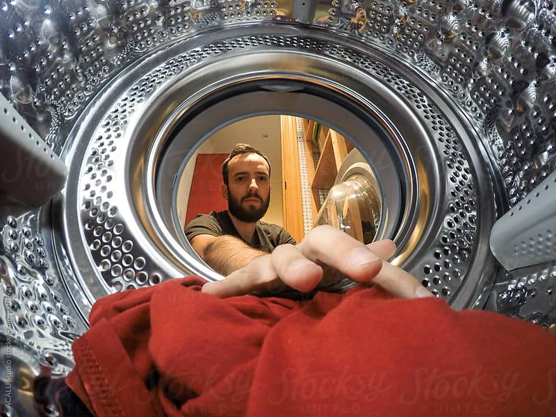 Man putting the washing machine by ACALU Studio for Stocksy United