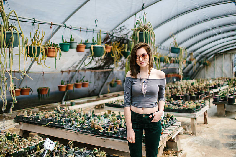 Portrait of a young woman in a cactus greenhouse by Kristen Curette Hines for Stocksy United
