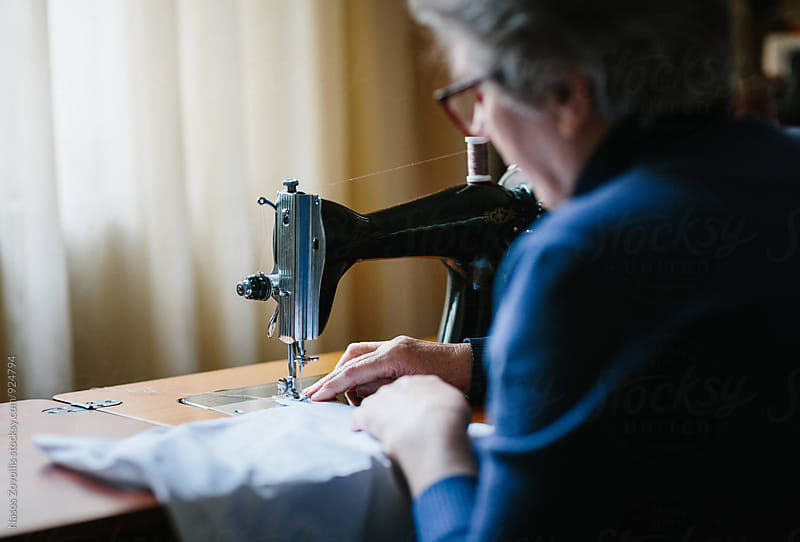 Senior woman working on a sewing machine by Nasos Zovoilis for Stocksy United