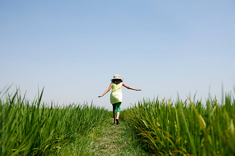 A girl walking through a greenfield with arms stretched by PARTHA PAL for Stocksy United