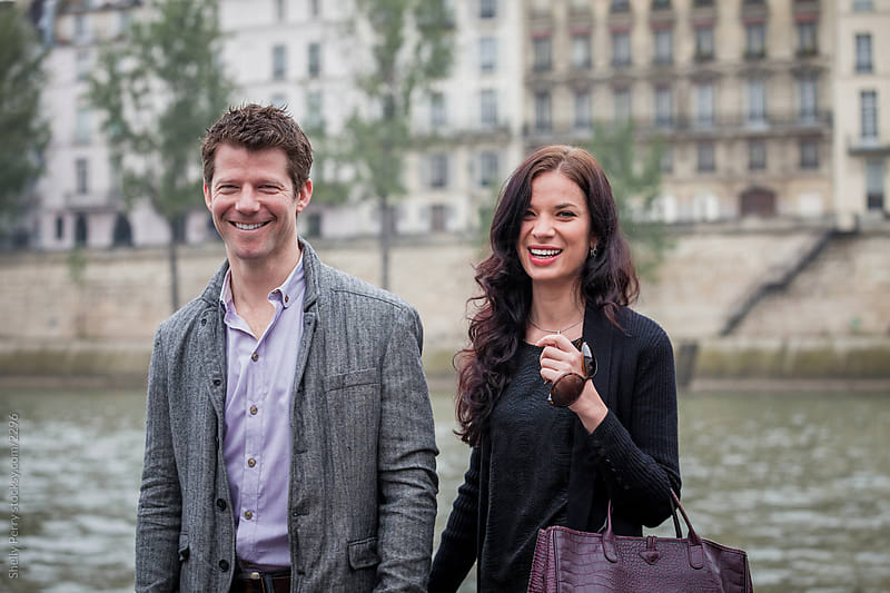 Smiling couple on the banks of the Seine River by Shelly Perry for Stocksy United