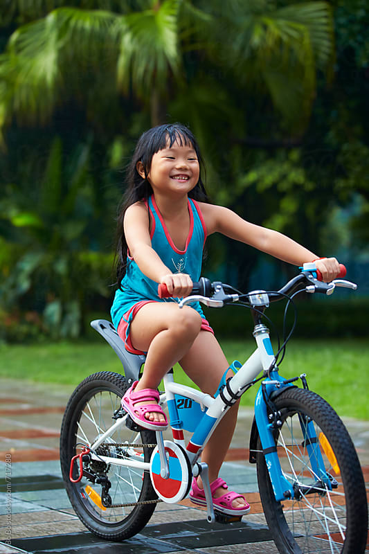 little asian girl riding bike outdoor by Bo Bo for Stocksy United