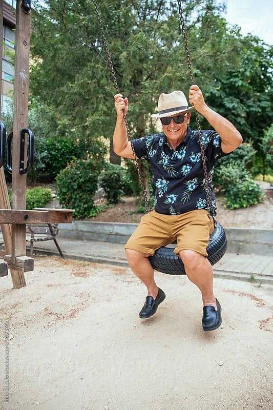 Senior man on swings by Inuk Studio for Stocksy United