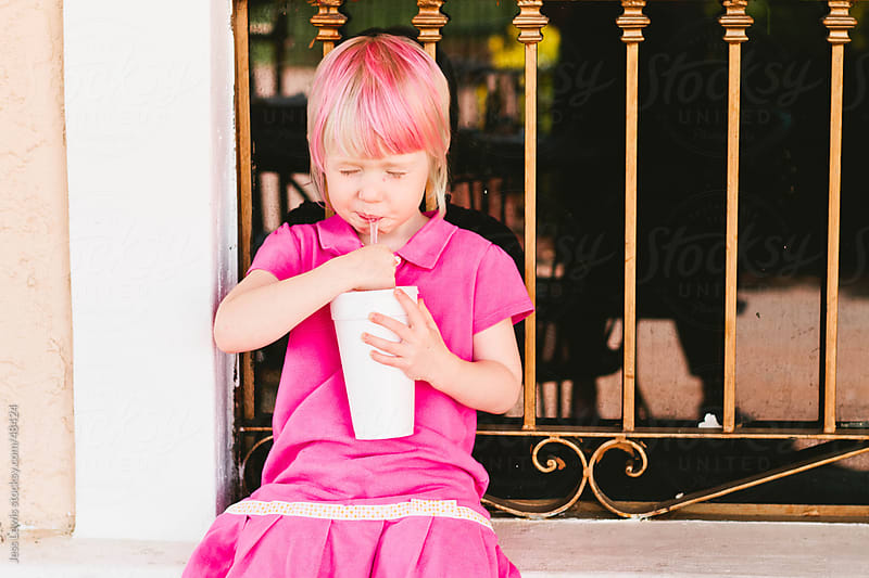 young girl with pink hair drinking from a straw by Jess Lewis for Stocksy United