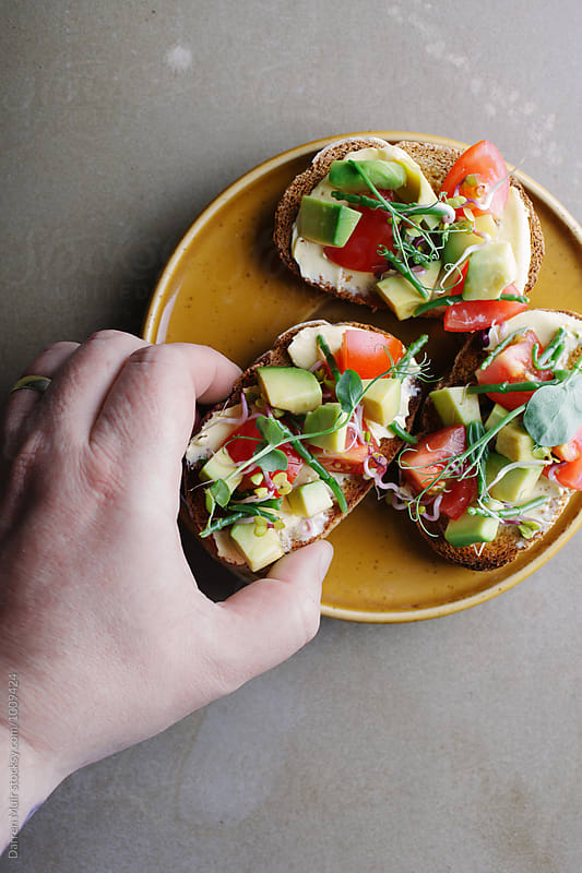Avocado,tomato and samphire toasts on a plate. Hand taking a slice of avocado toast from a plate. by Darren Muir for Stocksy United