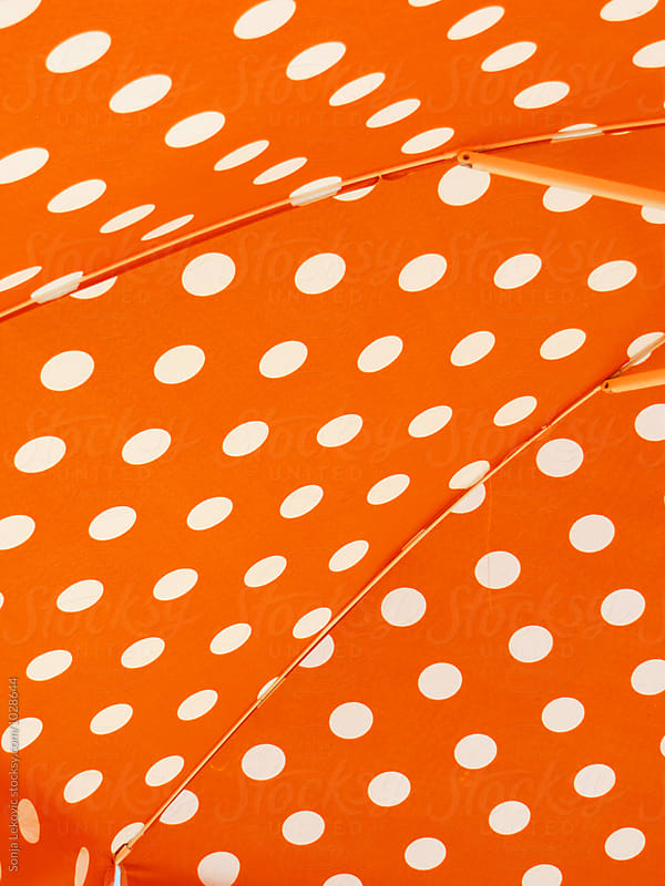 orange sun umbrella with white dots background by Sonja Lekovic for Stocksy United