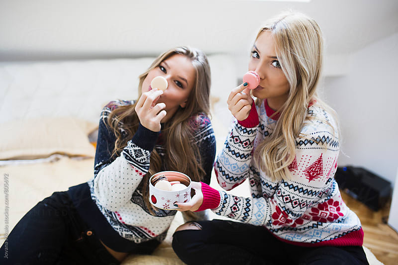 Two female friends eating french macaroons by Jovana Rikalo for Stocksy United