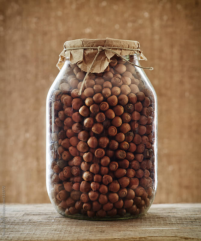 Still life of dried hazelnuts in a large glass jar by Trinette Reed for Stocksy United