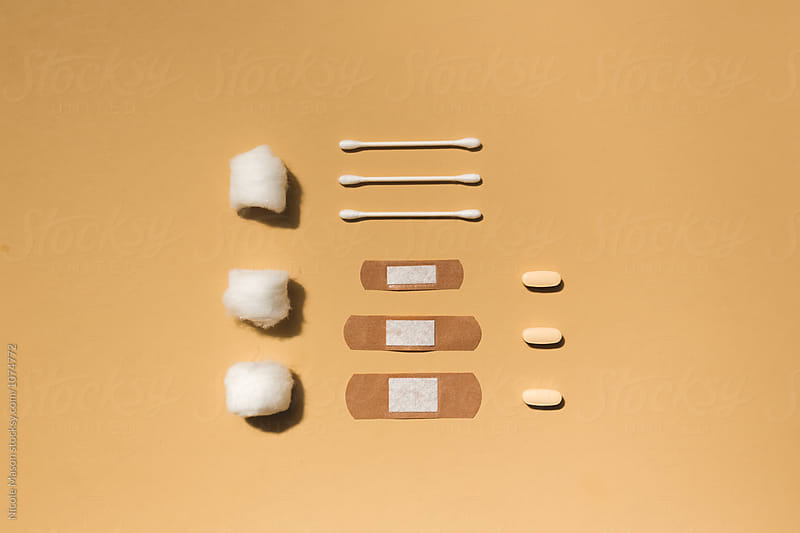 q-tip cotton swabs, bandaids and pills organized on orange background by Nicole Mason for Stocksy United