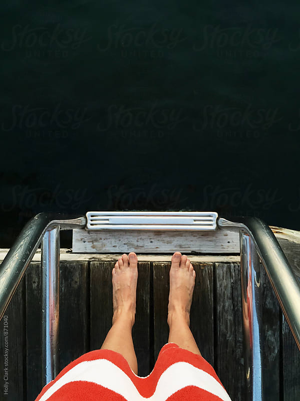Women's feet and legs on dock next to lake by Holly Clark for Stocksy United