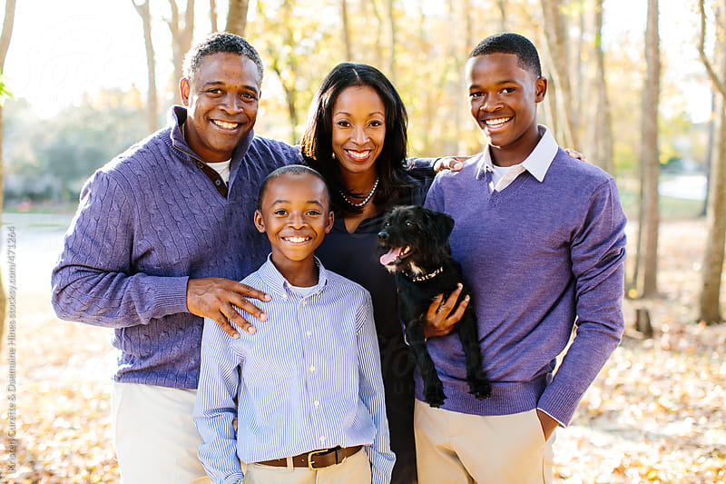 A beautiful African American family with their pet dog posing together by Kristen Curette Hines for Stocksy United