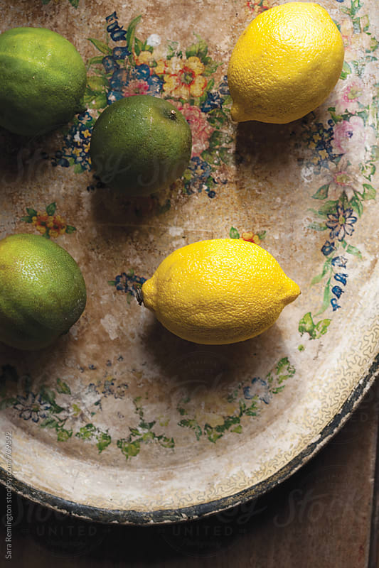 Organic Lemons and Limes on Platter by Sara Remington for Stocksy United