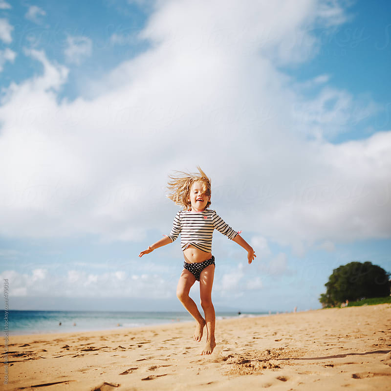 Cute young girl jumping free on sandy tropical beach in summer by Rob and Julia Campbell for Stocksy United