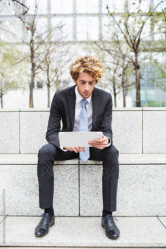Young man in a suit working with his digital tablet by michela ravasio for Stocksy United