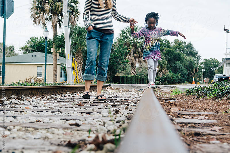 Mother helphing daughter balancing on a railway track by Gabriel (Gabi) Bucataru for Stocksy United