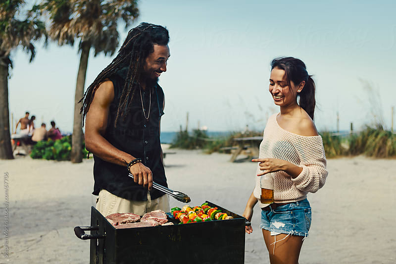 Man and Woman Grilling at the Beach by Stephen Morris for Stocksy United