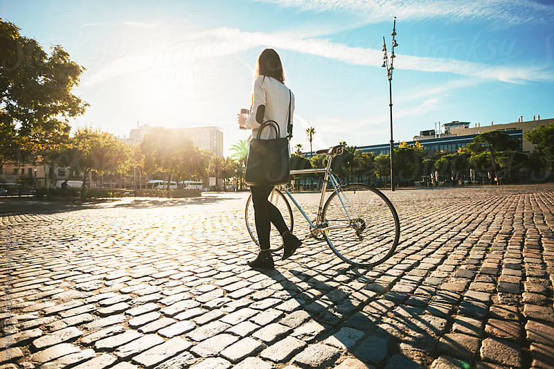 Back view of a businesswoman walking with her vintage bicycle on a sunny winter day. by BONNINSTUDIO for Stocksy United