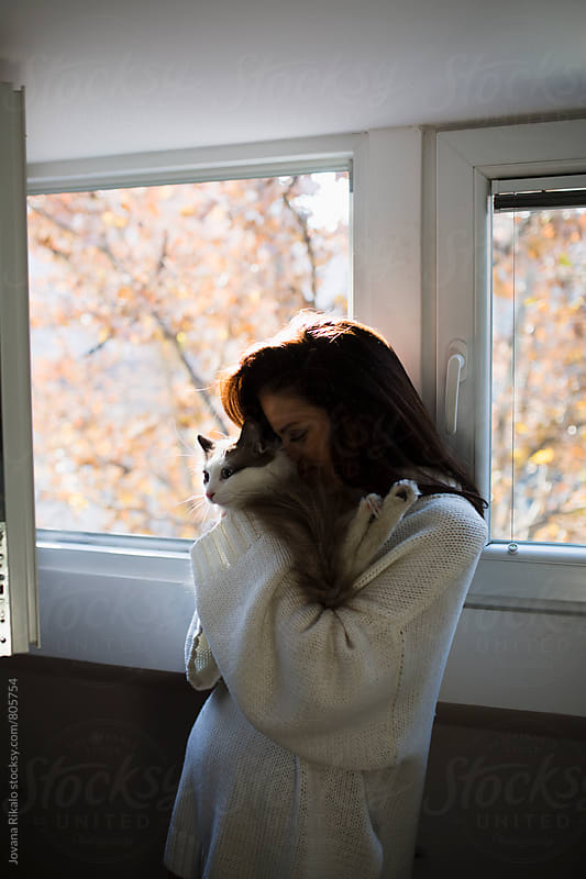 Young woman holding and kissing her cat by Jovana Rikalo for Stocksy United