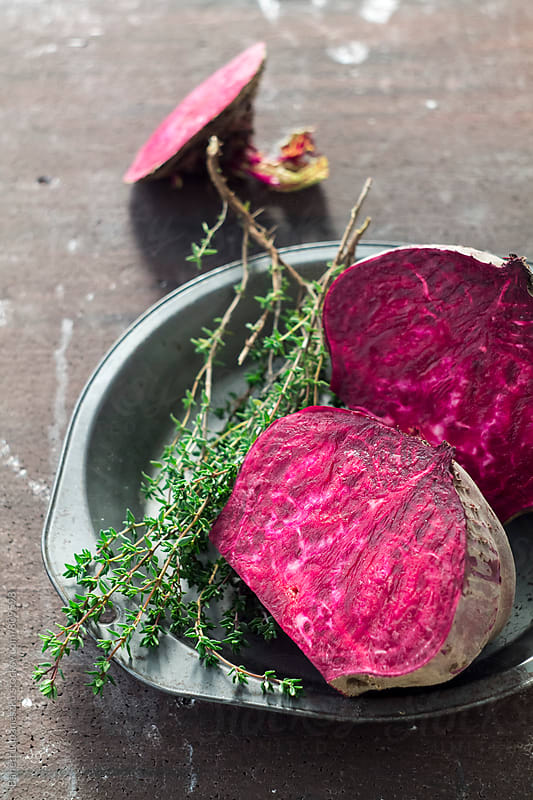Beets halved and thyme by Viktorné Lupaneszku for Stocksy United