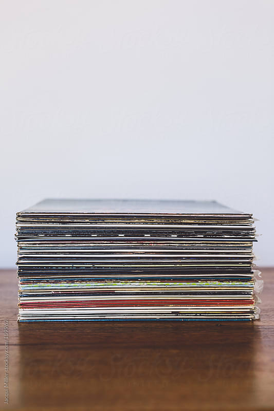 A stack of vinyl records on a wooden table by Jacqui Miller for Stocksy United