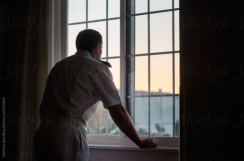 Military officer in navy uniform looking out window by Matthew Spaulding for Stocksy United